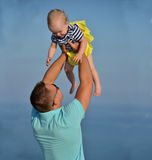 Happy young man father holding new born infant child baby girl t. Happy young men father holding new born infant child baby girl toddler on a blue sky sea Royalty Free Stock Photography