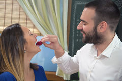 Happy young man feeding his girlfriend with a strawberry. Stock Photography