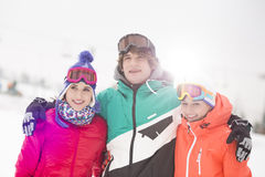 Happy young man with female friends standing arm around in snow Royalty Free Stock Photos