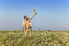 The happy young man in the field with a bouquet of camomiles Royalty Free Stock Images