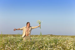 The happy young man in the field with a bouquet of camomiles Stock Images