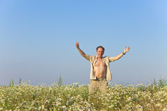 The happy young man  in the field of camomiles Royalty Free Stock Images
