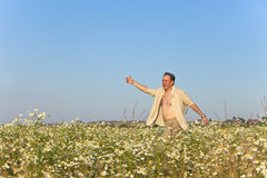The happy young man  in the field of camomiles Stock Photo