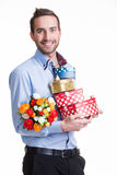 Happy young man with flowers a gift. Royalty Free Stock Image