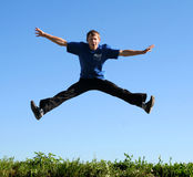 Happy young man flying in jump. Excited man flying above grass w Royalty Free Stock Image
