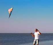 Happy young man with flying a kite on the beach Royalty Free Stock Images