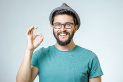 Happy young man gesturing OK sign. Everything is OK! Happy young man gesturing OK sign and smiling against gray background Royalty Free Stock Image