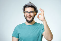 Happy young man gesturing OK sign. Everything is OK! Happy young man gesturing OK sign and smiling against gray background Royalty Free Stock Photography