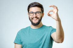 Happy young man gesturing OK sign. Everything is OK! Happy young man gesturing OK sign and smiling against gray background Royalty Free Stock Photo