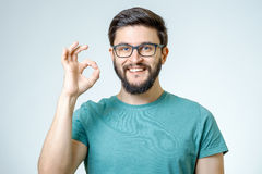 Happy young man gesturing OK sign. Everything is OK! Happy young man gesturing OK sign and smiling against gray background Stock Images