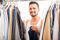 Happy young man getting dressed Stock Photography