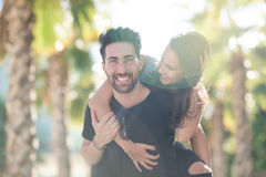 Happy young man giving his girlfriend a piggy back ride Royalty Free Stock Photo