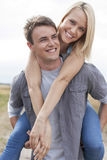 Happy young man giving piggyback ride to girlfriend on field Stock Photography