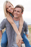 Happy young man giving piggyback ride to girlfriend on field Royalty Free Stock Photos
