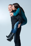 Happy young man giving a piggyback ride to her wife royalty free stock photos