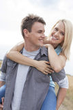 Happy young man giving piggyback ride to woman on field Stock Images