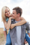 Happy young man giving piggyback ride to woman on field Stock Photo