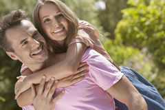Happy young man giving piggyback ride to woman in park Stock Photos