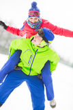 Happy young man giving piggyback ride to woman in snow Stock Photography