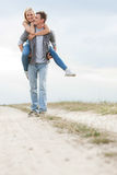 Happy young man giving piggyback ride to woman on trail at field Stock Photography