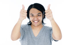 Happy young man giving thumbs up sign Royalty Free Stock Photos