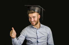 Happy young man graduating, with hat Stock Photography