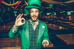 Happy young man in green suit stand in pub and hold golden coins. He look at one of them and amaze. Guy wear St. Patrick. `s suit royalty free stock photography