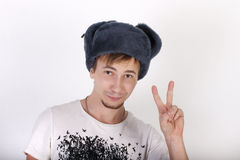 Happy young man in grey cap with earflaps shows gesture peace. In studio Royalty Free Stock Photos
