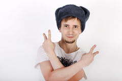 Happy young man in grey cap with earflaps. Shows two gesture peace Royalty Free Stock Photo