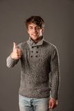 Happy young man in grey sweater showing thumb up Royalty Free Stock Photography
