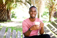 Happy young man on hammock with a coffee Stock Photos