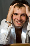 Happy young man with hands in hair Royalty Free Stock Images