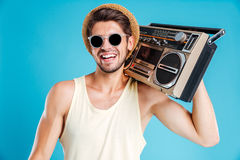 Happy young man in hat and sunglasses with boombox. Portrait of happy young man in hat and sunglasses with boombox Stock Photography