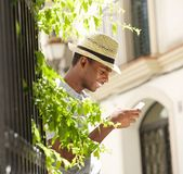 Happy young man with hat using mobile phone outside Stock Images