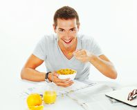 Happy young man having energetic breakfast Stock Images