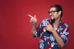 Happy young man in Hawaiian shirt pointing sideways against red Stock Photography