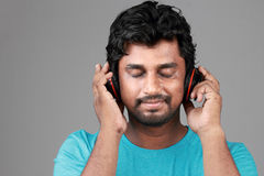A happy young man with a headphone. Young man listens music with headphones stock photography