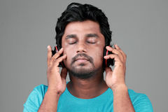 A happy young man with a headphone. Young man listens music with headphones stock photos