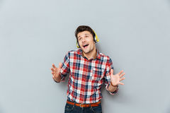 Happy young man in headphones listening to music and singing Royalty Free Stock Photography