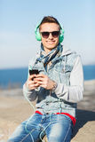 Happy young man in headphones with smartphone Stock Photography
