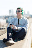 Happy young man in headphones with smartphone Royalty Free Stock Image