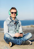 Happy young man in headphones with smartphone Stock Images