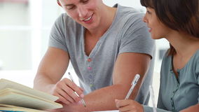 Happy young man helping a friend with her homework stock video footage