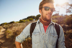 Happy young man hiking in countryside. Portrait of happy young man hiking in countryside. Caucasian male model with backpack hiking on sunny day. Summer vacation Stock Photography