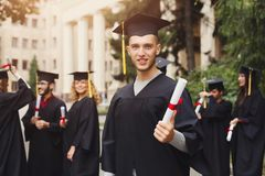 Happy young man on his graduation day. Young smiling men on his graduation day in university, standing with multiethnic group of students. Education Stock Images