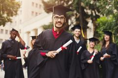 Happy young man on his graduation day. Young smiling men on his graduation day in university, standing with multiethnic group of students. Education Royalty Free Stock Photo