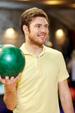 Happy young man holding ball in bowling club Royalty Free Stock Photo