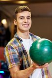 Happy young man holding ball in bowling club Royalty Free Stock Images