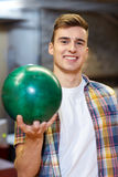 Happy young man holding ball in bowling club Stock Images