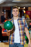 Happy young man holding ball in bowling club Stock Photo